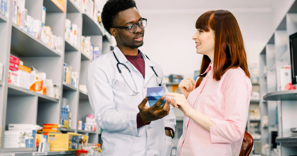 pharmacist showing medicine to woman